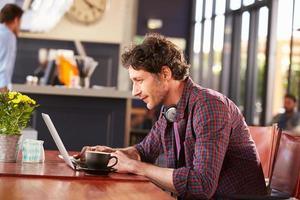 Mann, der am Computer am Kaffeehaus arbeitet foto
