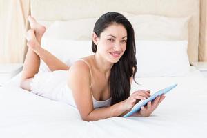 hübsche Brünette, die Tablet-Computer auf Couch berührt