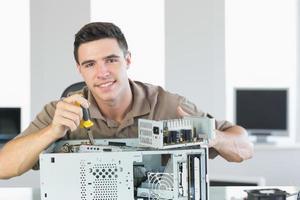 hübscher fröhlicher Computeringenieur, der offenen PC repariert foto