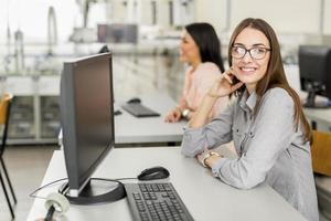 junges schönes Mädchen, das an einem Computer arbeitet foto