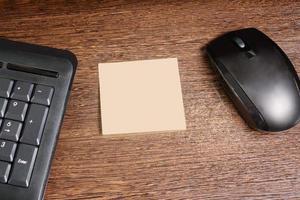 Komposition mit Aufkleber, Maus und Tastatur auf Holzschreibtisch foto