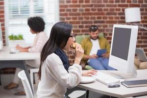 Gelegenheitsfrau, die Kaffee trinkt, während sie Computer benutzt