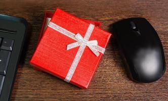 Komposition mit roter Geschenkbox, Maus und Tastatur foto