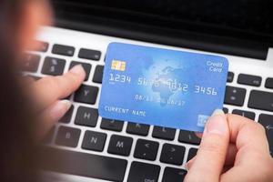 Person, die Kreditkarte mit Laptop hält