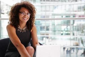 junge Geschäftsfrau, die Laptop-Computer benutzt und Kamera schaut foto