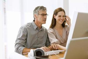 Geschäftsmann und eine Geschäftsfrau, die an einem Computer arbeiten foto