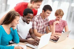 ethnisch unterschiedliche Gruppe von Studenten, die Laptops benutzen foto