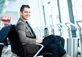 moderner Geschäftsmann, der Tablet-Computer am Flughafen verwendet