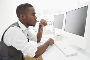 fokussierter Geschäftsmann, der Brille hält und Computer benutzt
