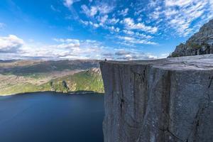 Tourist, der am berühmten Kanzelfelsenrand in Norwegen sitzt