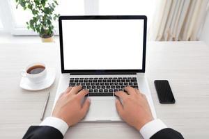 Geschäftsmann sitzt hinter einem Laptop mit isoliertem Bildschirm foto
