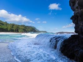 Am Lumahai Beach in Kauai fließen mächtige Wellen über Felsen foto