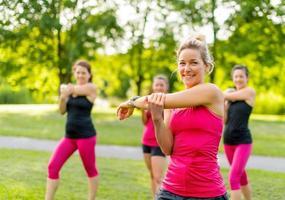 lächelnder Jogging-Trainer, der sich im Park ausdehnt foto
