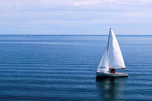 weißes Segelboot im blauen Ozean foto