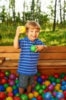 glückliches Kind, das mit bunten Plastikkugeln spielt foto