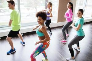 Gruppe lächelnder Leute, die im Fitnessstudio oder im Studio tanzen foto