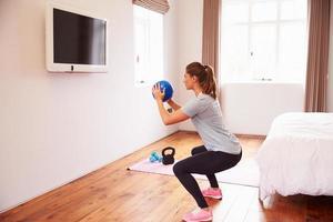 Frau, die zur Fitness-DVD im Fernsehen im Schlafzimmer ausarbeitet