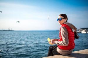 Frau sitzt auf einem Felsvorsprung mit Blick auf Wasser mit Kopfhörern