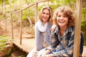 Geschwister sitzen auf einer Holzbrücke in einem Wald, Porträt