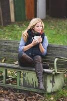 lächelnde modische Blondine, die heißes Getränk trinkt foto