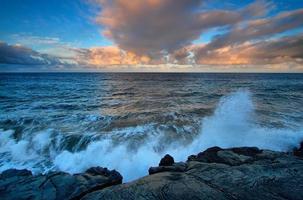 Blick auf das Meer und die schwarzen Lavasteine bei Sonnenuntergang foto