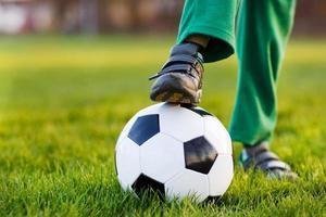 blonder Junge von 4, der Fußball mit Fußball nur Feld spielt