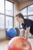 junger Mann, der einen Fitnessball benutzt, um zu trainieren foto