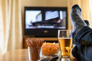 Fernsehen (Film) mit Füßen auf dem Tisch und Snacks foto