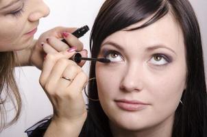 Maskenbildner färbt Wimpernmodell foto