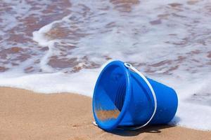 umgestürzter Eimer am Strand foto