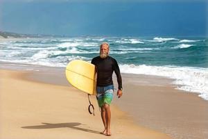 Surfer am Meer steht mit einem Surfbrett foto