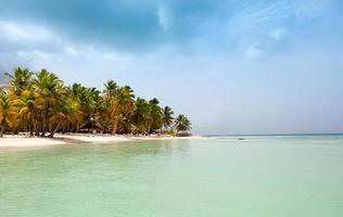 Blick vom Meer auf einen tropischen Strand und eine Insel