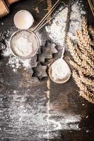 Weihnachten backen hölzernen Hintergrund mit Cutter, Mehl, Löffel und Ohren foto