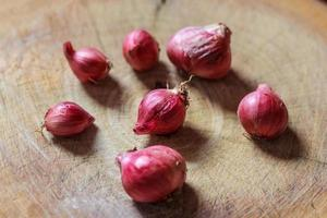 rote Zwiebeln auf einem hölzernen Hintergrund, Holzhackblock foto
