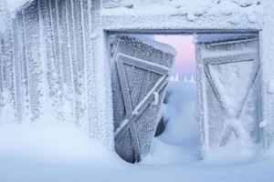 winterwonderland - verlassenes Bauernhaus im Winter mit tiefem Schnee bedeckt foto