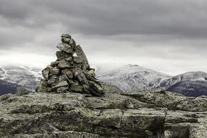hügelige Landschaft mit einem Meilenstein aus Steinen im Vordergrund foto