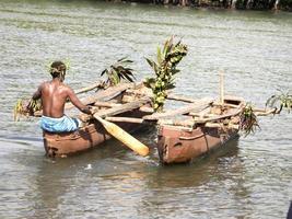 ein Stammesmann, der zwei Kanus schiebt foto