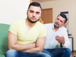 männliche Erwachsene streiten sich über etwas foto