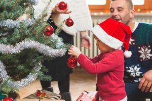 Kind mit Familie, die den Weihnachtsbaum schmückt foto