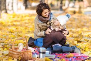 glückliche Mutter, die mit ihrer Tochter auf der Decke sitzt foto