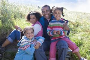 Porträt der Familie, die auf Gras sitzt