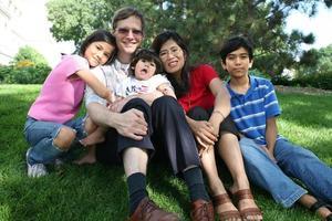 große gemischtrassige Familie sitzt auf Rasen