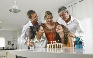Familie sitzt um eine Geburtstagstorte foto
