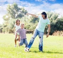 dreiköpfige Familie spielt mit Ball foto