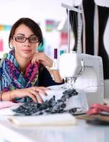 junge Frau, die beim Sitzen an ihrem Arbeitsplatz näht foto