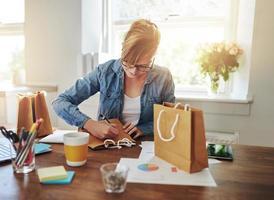 junge Geschäftsfrau, die Verpackung entwirft foto