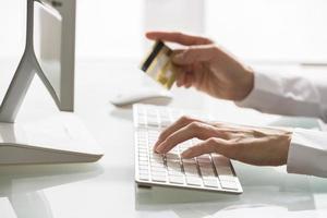 Frau, die mit Computer und Kreditkarte einkauft foto