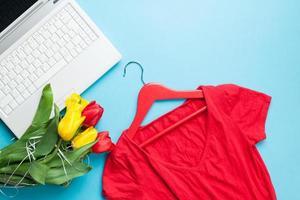 weißer Computer und Tulpenstrauß mit Kleiderbügel