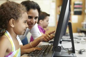 Grundschüler mit Lehrer im Computerunterricht
