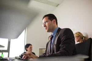 schöner Geschäftsmann, der mit Computer im Büro arbeitet foto